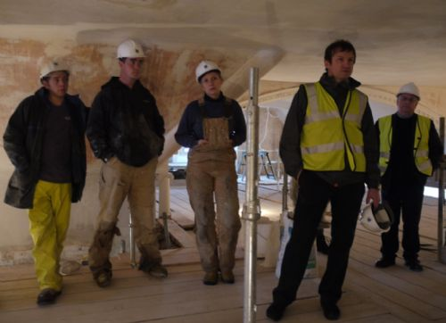 Denis Forrest advises from the back (far right) during a discussion on plastering